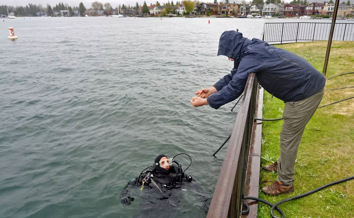 a scuba diver in the water speaking to a man on shore